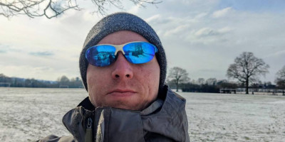 Calum wearing blue sun glasses at a snow-covered field in Tonbridge