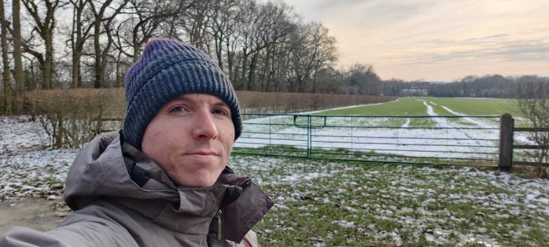 Calum beside a green gate in tree-lined countryside with some snow on the field