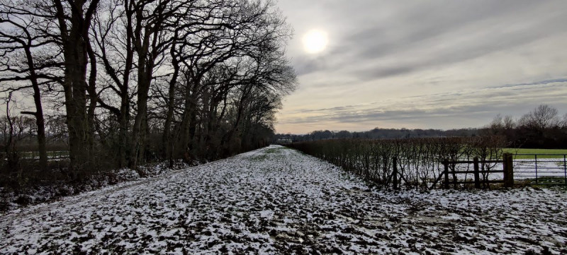 Bridle path near Tonbridge with melting snow and sun peaking through clouds