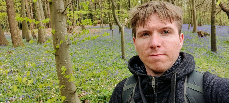 Calum with backdrop of bluebell covered forest