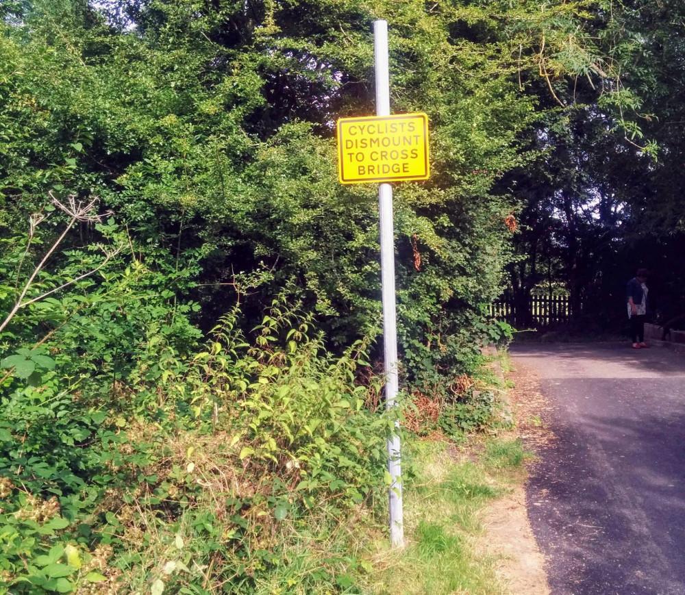 Yellow signpost - cyclists dismount to cross bridge on roadside
