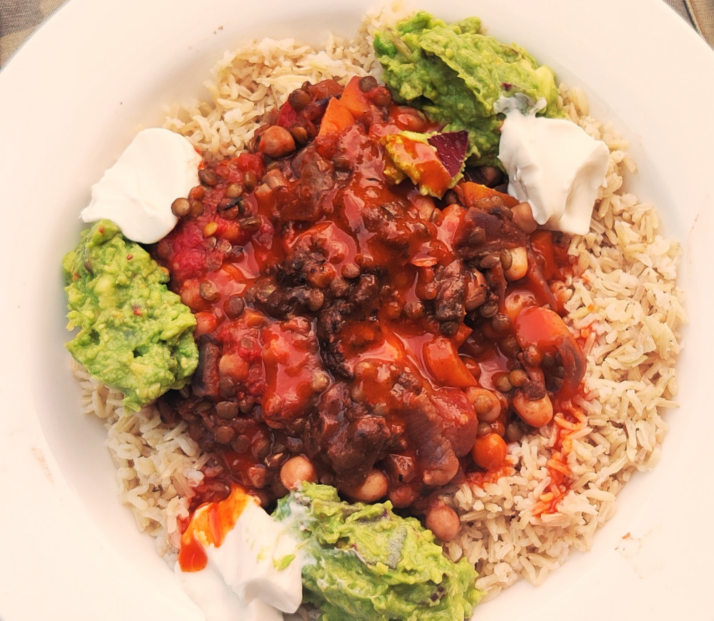 Vegan chili dish surrounded with brown rice