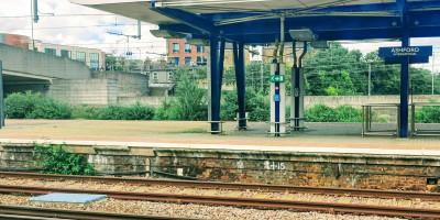 Ashford International station with green foliage growing alongside the platform edge