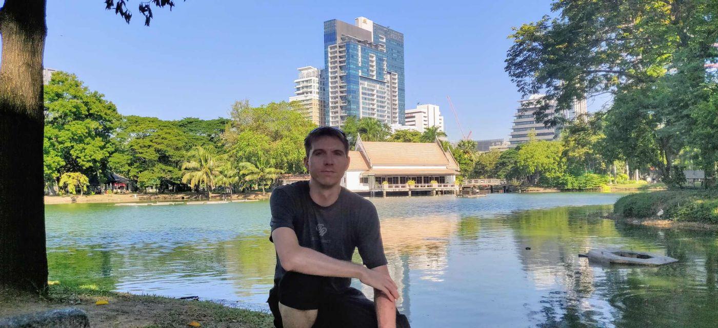 Calum perching by a lake in Lumphini Park